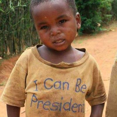 """Un petit garçon noir avec un tee shirt ecrit """"Je peux ête President - I can be president"""""""