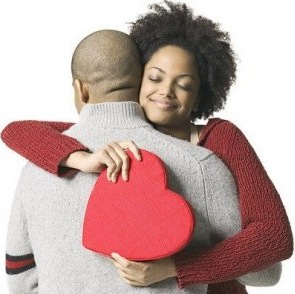 Un homme et une femme (noirs) qui s'embrassent avec un gros coeur rouge pour la St valentin