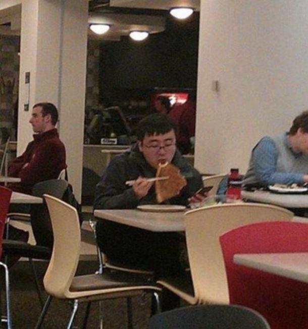 3. Un homme qui mange sa pizza avec des baguettes