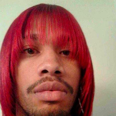Un homme noir avec les cheveux longs défrisés et colorés