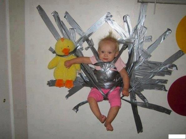 Un bébé accroché au mur avec du scotch