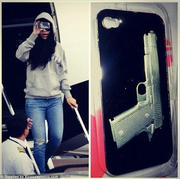 Rihanna montrant que la coque de son téléphone portable représente une arme à feu (été 2012).